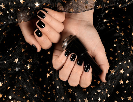 Woman with black manicure holding nail polish bottle over dark fabric, top view