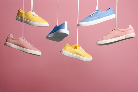 Bright stylish shoes hanging against color background