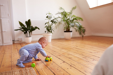 Baby Boy Playing With Toys On Floor At Home