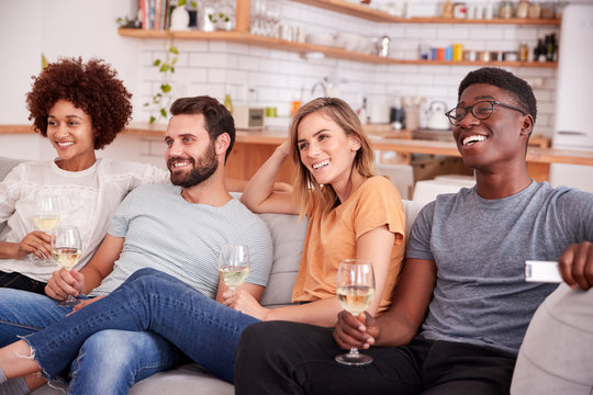Group Of Friends Sitting On Sofa And Watching Movie At Home Whilst Drinking Wine