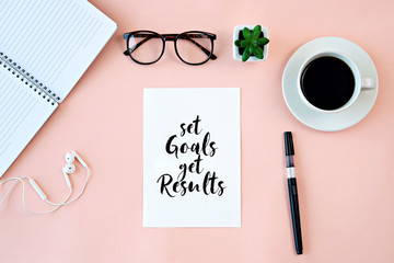"Inspirational quotes ""Set Goals Get Results"" on card, cup of coffee, notebook and pen on pink background"