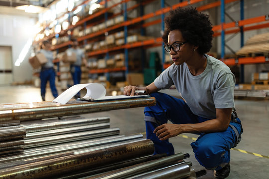 Black female worker checking list of products in a warehouse.