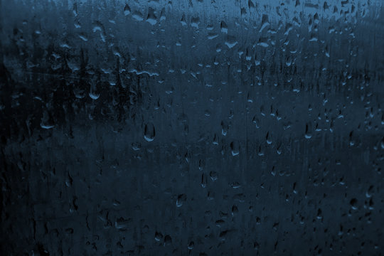 Rain drops on blue glasses surface or  metal. Pattern of raindrops. Water drops on glass texture background. Little blurred. Banner for text.