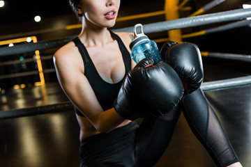 cropped view of athletic woman in boxing gloves holding sport bottle