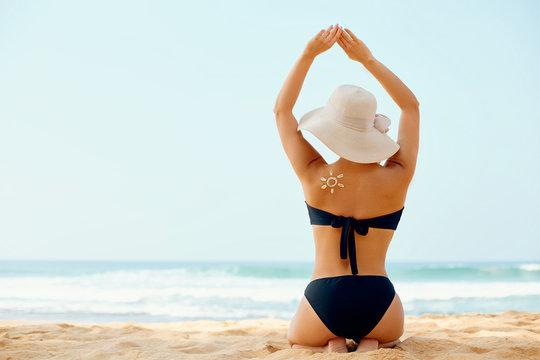 Beautiful woman in bikini applying sun cream on tanned shoulder. Sun protection. Skin and body care. Girl using sunscreen to skin. Portrait of female holding suntan lotion and moisturizing sunblock.