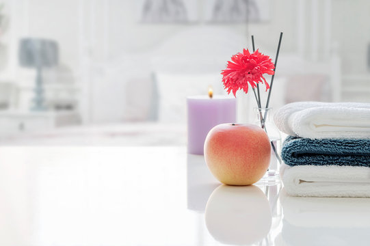Stack of clean towels on white table with blur background of bed room.
