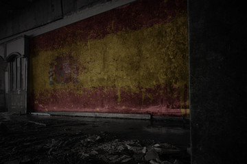 painted flag of spain on the dirty old wall in an abandoned ruined house.