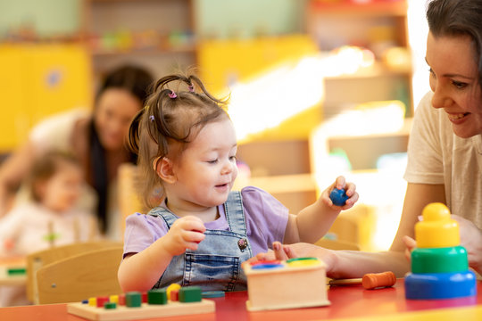 Babies with teachers playing with developmental toys in nursery
