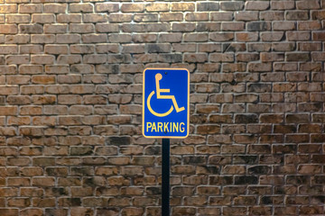 Handicap parking sign against a stone brick wall illuminated by sunlight