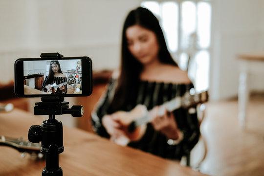 blogger live broadcasting music instrument tutorial on social media. vlogger recording online vlog video.