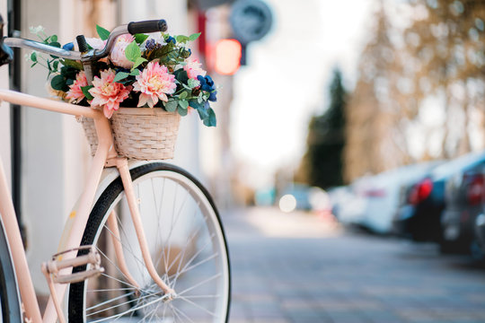 White bicycle with basket of flowers standing near the door on the street in city.