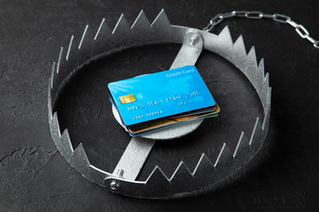 Trap with stack of credit cards. Unsafe credit risk. Black background. Wall mural
