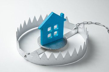 Trap with bait house. The risk of buying an old house. Dangerous mortgage. Home insurance. Gray background.