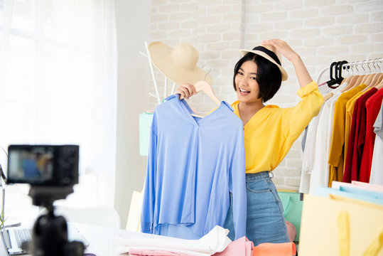 Young Asian woman fashion vlogger trying on clothes and accessories