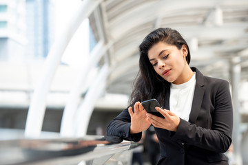 Young Latin businesswoman using smartphone outdoors