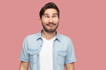 Portrait of crazy handsome bearded young man in blue casual style shirt standing with crossed eyes and looking with funny comedian face. indoor studio shot, isolated on pink background.