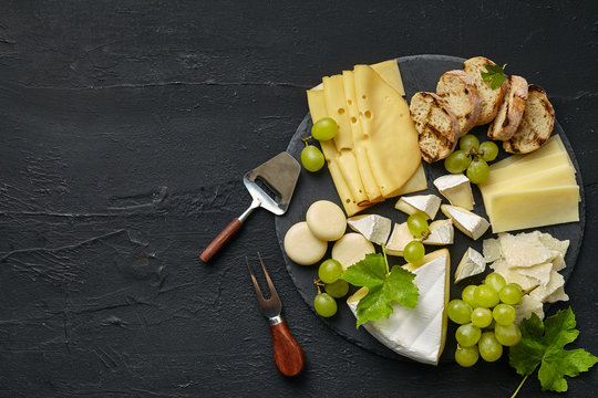 Top view of tasty cheese plate with fruit, grape on a circle kitchen plate on the black stone background, top view, copy space. Gourmet food and drink.