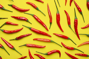 Red hot chilli pepper on yellow background