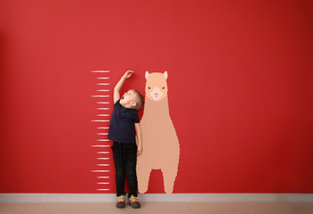 Surprised little boy measuring height near color wall