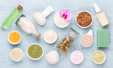 Sea salt, aromatherapy oil in bottles and orchid on vintage wooden background.