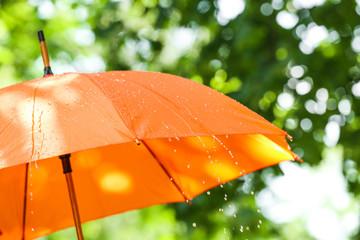 Bright umbrella outdoors on rainy day Fotobehang