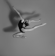 Flexible gymnast. Girl makes an expressive jump. Black and white photo.