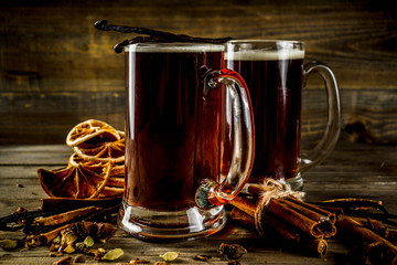 Hot beer with spices - vanilla, cinnamon, anise, citrus. Mulled dark beer drink. Dark wooden background copy space