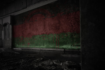 painted flag of malawi on the dirty old wall in an abandoned ruined house.