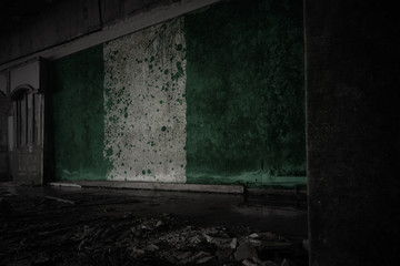 painted flag of nigeria on the dirty old wall in an abandoned ruined house.