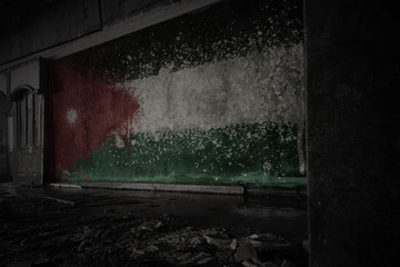 painted flag of jordan on the dirty old wall in an abandoned ruined house.