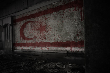 painted flag of northern cyprus on the dirty old wall in an abandoned ruined house.