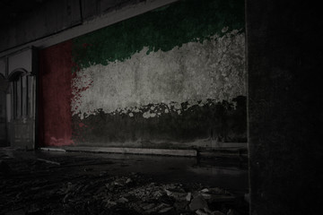 painted flag of united arab emirates on the dirty old wall in an abandoned ruined house.