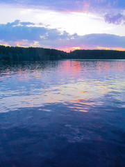 Wall Mural - Bright colorful sunset over a lake. Beautiful reflection by a tranquil water of amazing sky and the lakeside at sundown in the summer evening. Lake Elovoe (Spruce Lake), South Ural, Russia.
