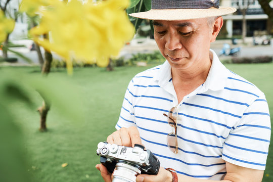 Asian senior professional in casual wear and in hat standing outdoors and looking just made photos on digital camera