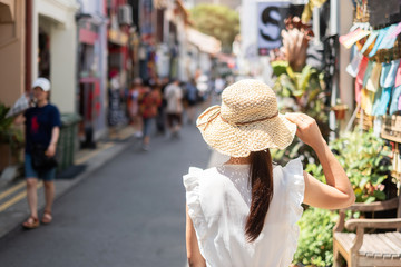 Young woman traveling with white dress and hat, happy Asian traveler walking at Haji Lane and Arab...