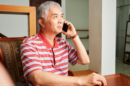 Asian senior man wearing striped casual clothing sitting at the table and listening to somebody on mobile phone at home