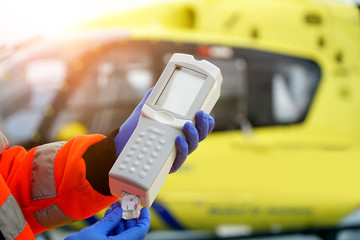 Doctor of an air ambulance in front of a rescue helicopter holds a blood test device