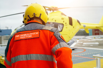 Doctor of an air ambulance runs to a rescue helicopter for an emergency operation