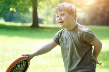 Little boy with down syndrome plays a ball game in the park