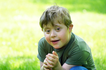 Portrait of a little boy with down syndrome while playing in a park