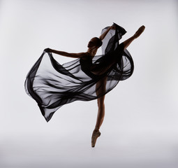 A ballerina dances with a black cloth