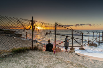 Two women silhouetted looking to the sunrise through a fence that runs into the ocean fence has memorabilia hanging on it in remembrance of the past  White Plains Fence-line, Hawaii