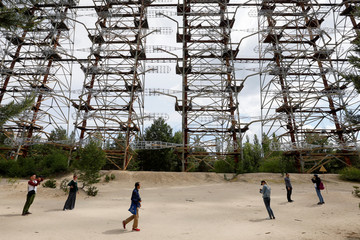 """Visitors inspect constructions of a former Soviet Union over-the-horizon (OTH) radar system """"Duga"""" near the Chernobyl Nuclear Power Plant, near Chernobyl"""