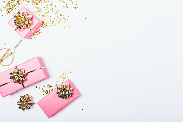 Festive pink gift boxes with golden bows