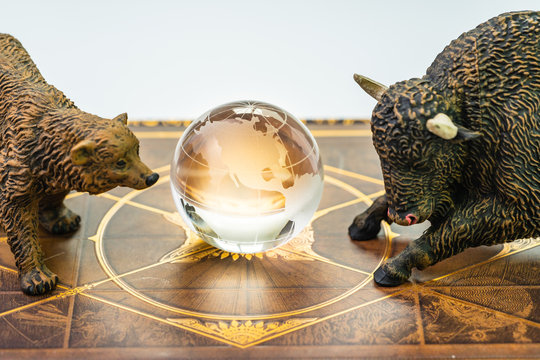 Bull and bear market, world stock exchange symbol for high and low season concept, bear and bull figures with the shinny globe with US America map in the middle