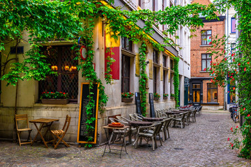 Old street with tables of restaurant in Antwerpen, Belgium. Cozy cityscape in Antwerpen