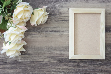 Wooden photo frame and flower on wood background