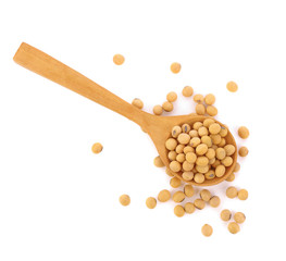 Soybeans in wooden spoon on a white background. Top view