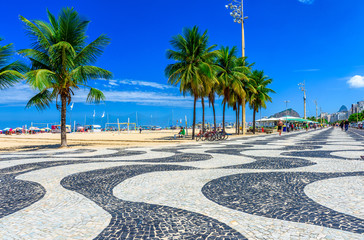 Fotomurales - View of Copacabana beach with palms and mosaic of sidewalk in Rio de Janeiro, Brazil
