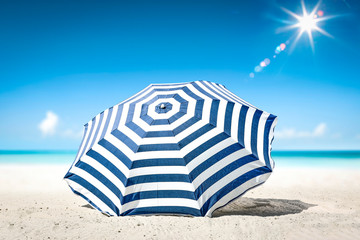 Obraz Summer background of umbrella with free space for your decoration on hot sand. Sunny day and ocean landscape.  - fototapety do salonu
